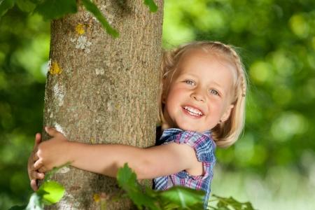 아름 다운 금발 소녀 사랑스러운 행복 한 미소로 카메라를보고 나무를 포옹 스톡 콘텐츠