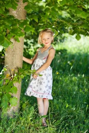 petite fille avec robe: Belle petite fille dans une robe été, debout sous un arbre à feuilles vertes dans un champ herbeux souriant timidement à la caméra Banque d'images