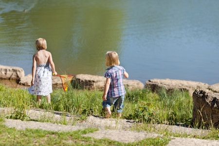 Two little girls with their backs to the camera fishing at the lake with a small net in summer sunshine photo