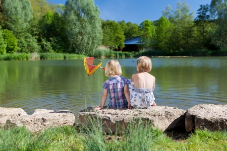 children pond: Rear view of two little blond girls sitting close together side by side on a rock fishing at the lake with a small net
