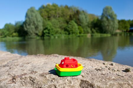 small boat: Little colourful plastic toy boat at the lake lying abandoned on a rocky ledge overlooking the calm water