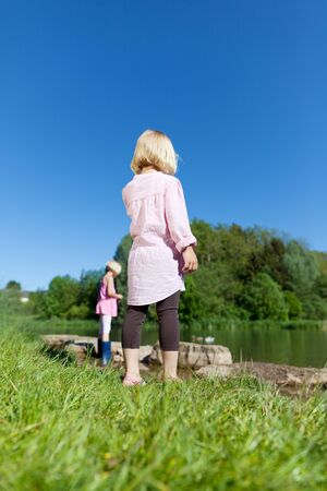 Low angle view of two little blond children, both girls, playing at the lake photo