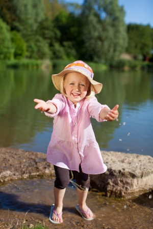 imploring: Adorable young girl in a sunhat at the lake holding out her arms stretching towards the camera as though imploring a loving hug