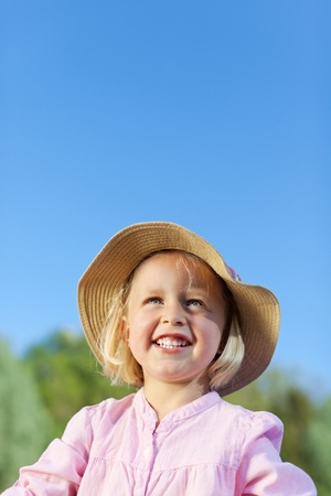 Portrait of a beautiful little summer child with a low angle view of a smiling little blond girl in a straw sunhat photo