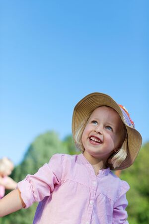 Laughing beautiful little blond girl in a straw hat playing outdoors on a summer day photo