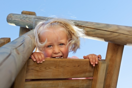 Blond young child playing in the play ground