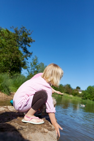 crouched: Little girl playing on a lake shore bending down trailing her hand in the calm water