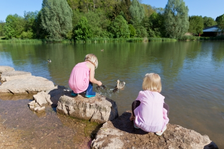 Two small girls feeding ducks on a lake squatting down on rocks at the waters edge photo