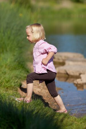 Portrait of cheerful young girl walking inside the river photo