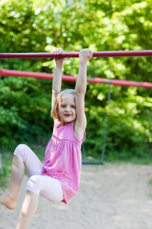 Little girl playing on metal bars hanging from her hands kicking her feet in the air in a leafy green playground photo
