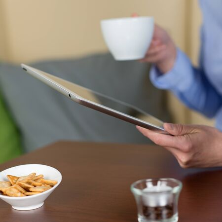Close-up of a woman reading from a tablet in the coffee shop while drinking a cup of coffee photo