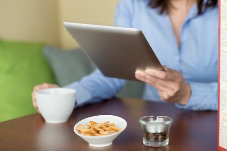 Woman reading from a tablet in the coffee shop with a cup of coffee and snacks photo