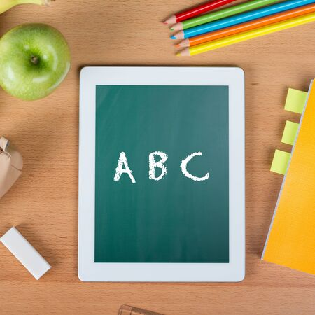Digital tablet on a school desk with ABC written between a paper notebook, pencils, an eraser, and an apple photo