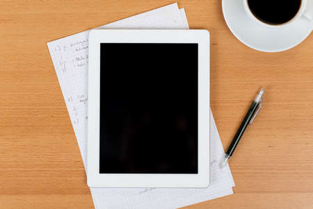 Digital tablet with a black empty display over a desk with notes written on paper sheets and a cup of black coffee Stock Photo - 21265405