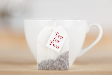 Closeup of tea bag with text and cup on table photo