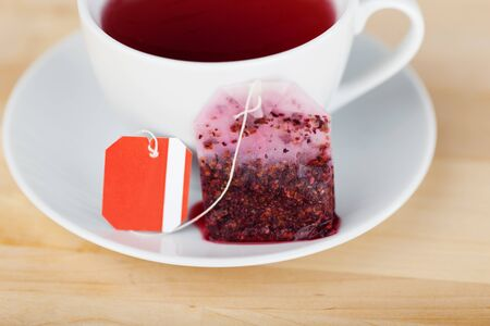 teabag: Closeup of tea bag and cup on wooden table