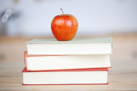 stacked books: Closeup of red apple on stacked books on table