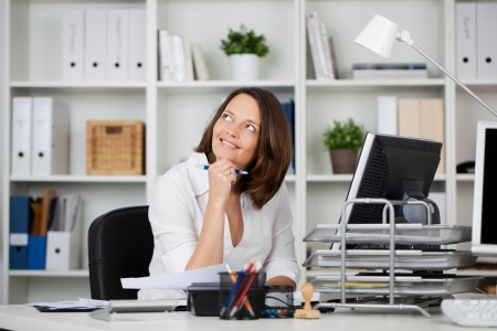 contented: Portrait of businesswoman thinking at her office table