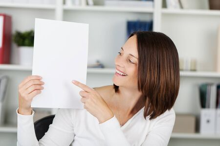 Smiling woman pointing at the white paper photo