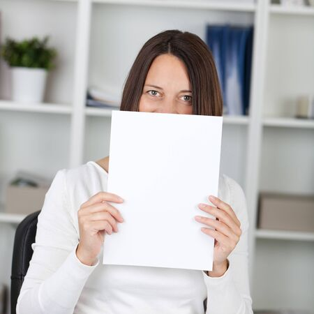 obscured face: Portrait of mid adult businesswoman holding blank paper in front of face at office