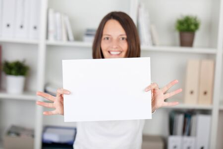 Happy woman shows the white empty paper inside the office photo