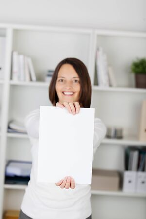 Happy female holding white empty paper inside the office photo