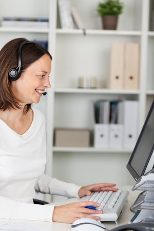 Happy call center agent working with headset in front of computer photo