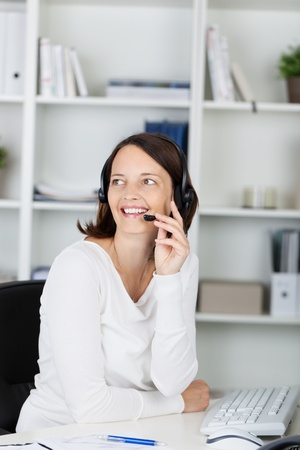 conversing: Mid adult businesswoman conversing on headset at office table