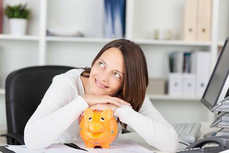 piggybank: Smiling female looking at something with piggybank