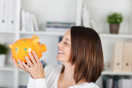 coinbank: Happy female looking at the piggy bank in a close up shot