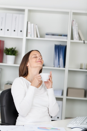 work break: Young woman enjoys her coffee break before continuing with her work. Stock Photo