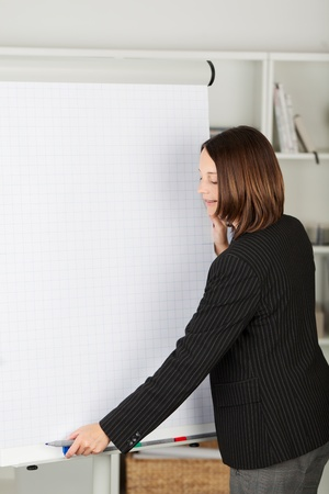 Young businesswoman in a black jacket starting a presentation in office photo