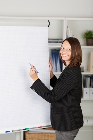 Young businesswoman in a black jacket writing on a blank flipchart with a marker pen during a presentation photo