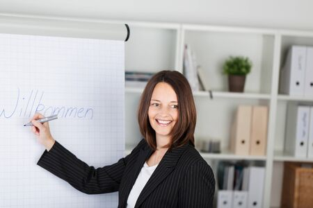 Portrait of happy businesswoman writing welcome sign on paper at office photo