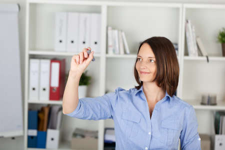 glassboard: Smiling businesswoman writing on invisible screen in office