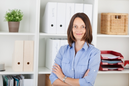 Portrait of confident businesswoman with arms crossed standing in office photo