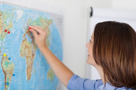attaching: Closeup of businesswoman attaching pushpin on map in office Stock Photo
