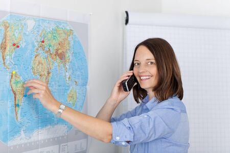 worldmap: Portrait of happy businesswoman conversing on cordless phone in office