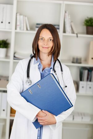 facing: Attractive young female doctor with a stethoscope around her neck carrying a large file and standing looking at the camera