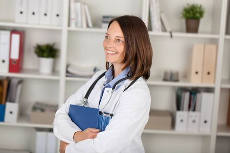 Happy female doctor with binder looking away against shelves in office photo