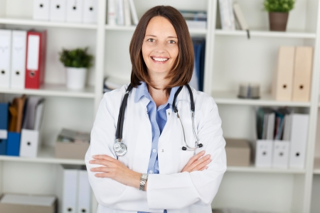 Portrait of confident female doctor with arms crossed standing against shelves in office photo