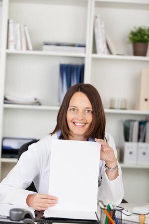 Mid adult female doctor displaying blank paper while looking at camera in office photo