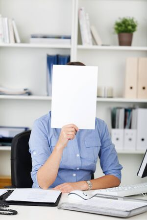 Businesswoman holding a blank white sign with copyspace for your advert or text in front of her face as she sits at her desk in the office photo