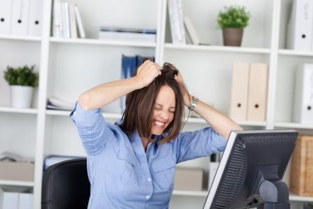 clenching teeth: Irritated businesswoman pulling her hair while sitting in office