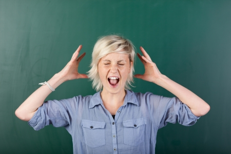 Young blonde woman with eyes closed shouting in front of chalkboard Stock Photo