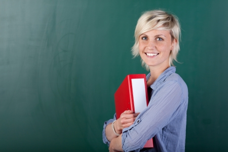 sexy teacher: A smiling young student standing in front of the blackboard and holding a folder.