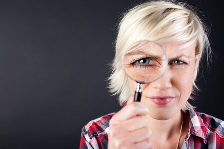 Closeup portrait of a young woman with magnifying glass against black background Stock Photo - 21266097