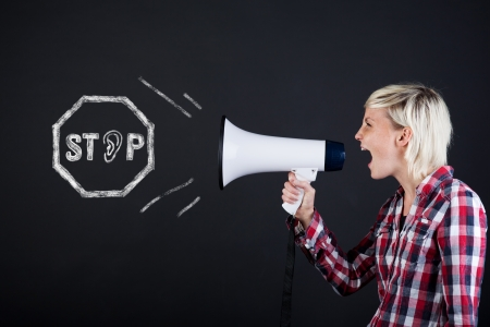 angry person: Side view of a young woman yelling into the megaphone against black background Stock Photo