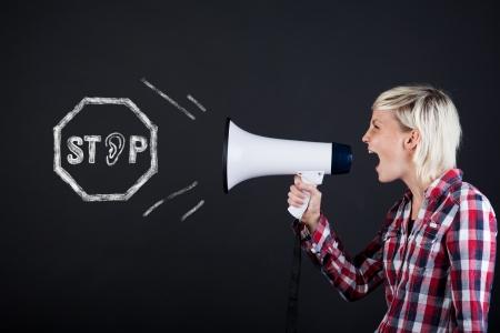 persona enojada: Vista lateral de una mujer joven que grita en el megáfono sobre fondo negro Foto de archivo