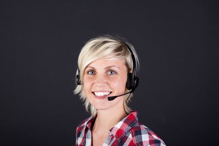 Closeup portrait of a pretty young woman with headset against black background Stock Photo - 21266107